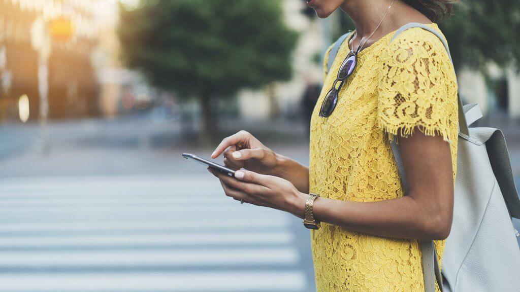 woman using phone outside on city sidewalk