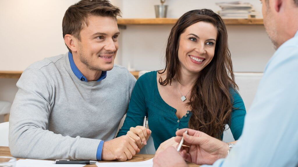 excited couple gazing at salesperson