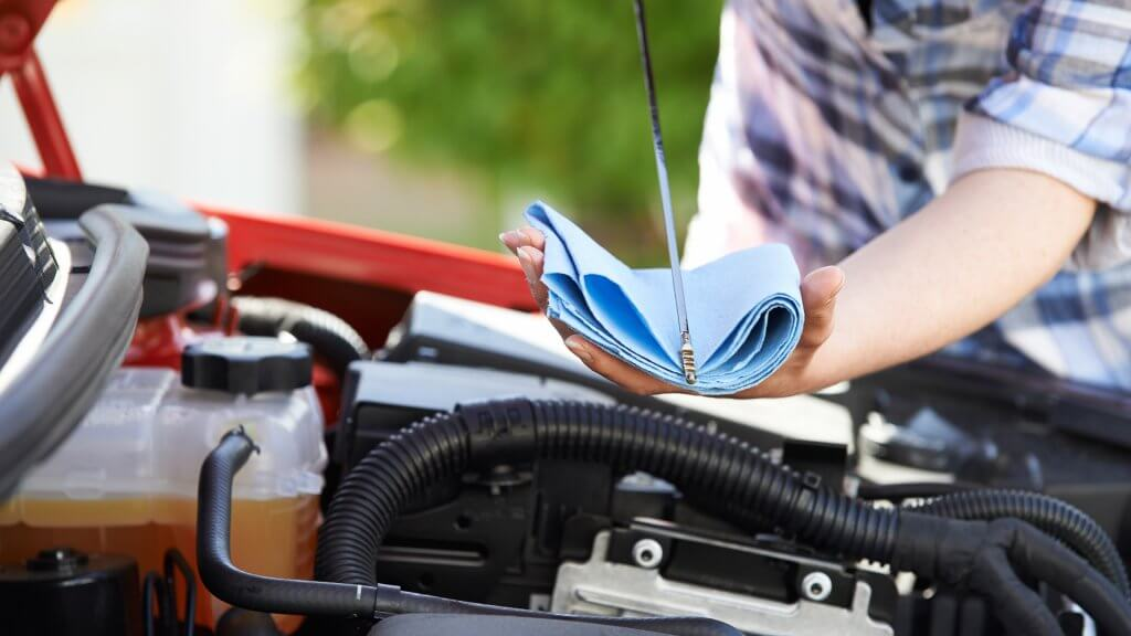 man using towel to check oil levels in car