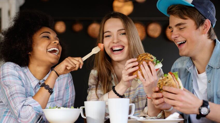 Group of young friends eating burgers and a salad