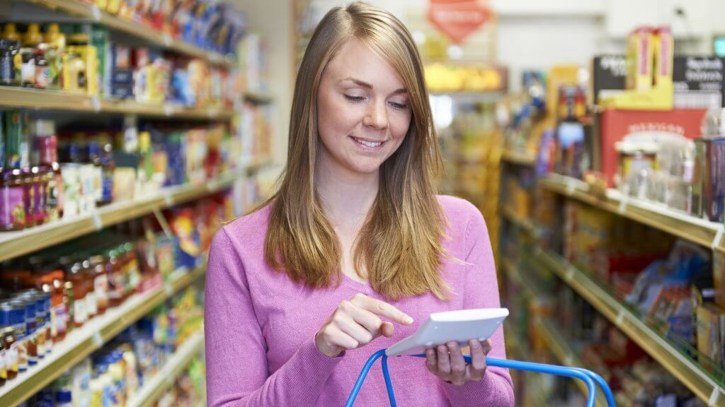 woman using calculator while grocery shopping