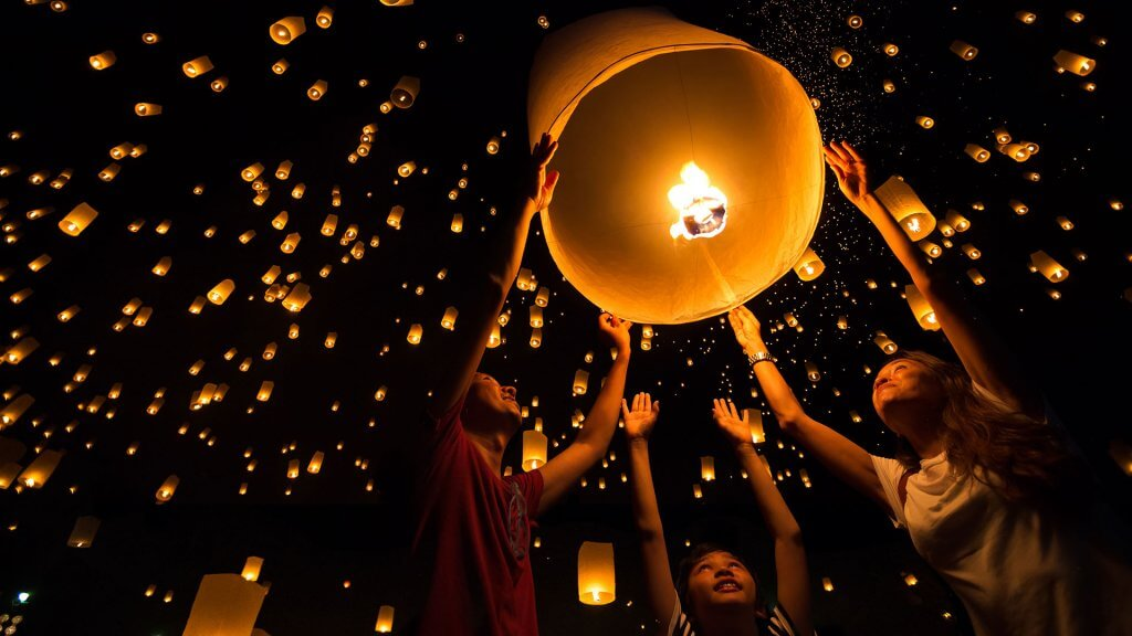 people releasing Chinese lanterns into the night sky
