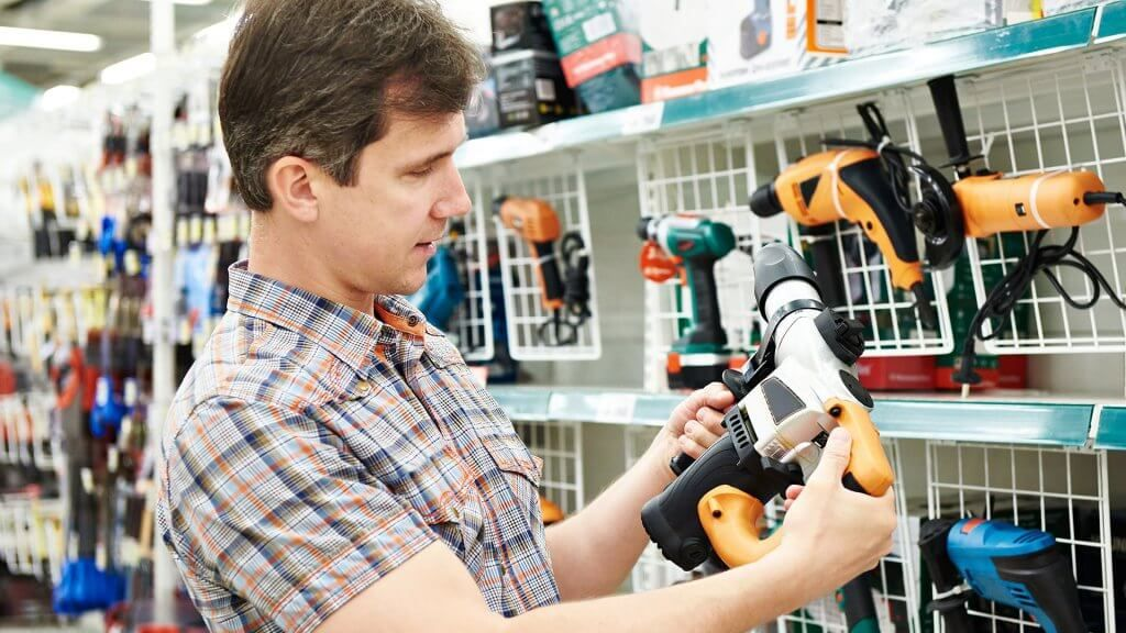 man looking at power drill in hardware sore