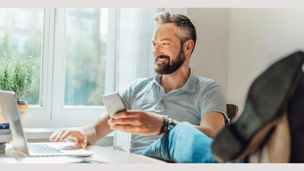 handsome older man using conducting research on smartphone and laptop
