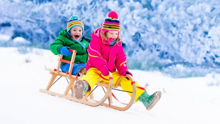 little boy and girl riding down hill on sled together
