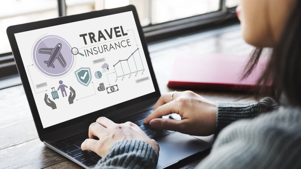 woman researching travel insurance on computer