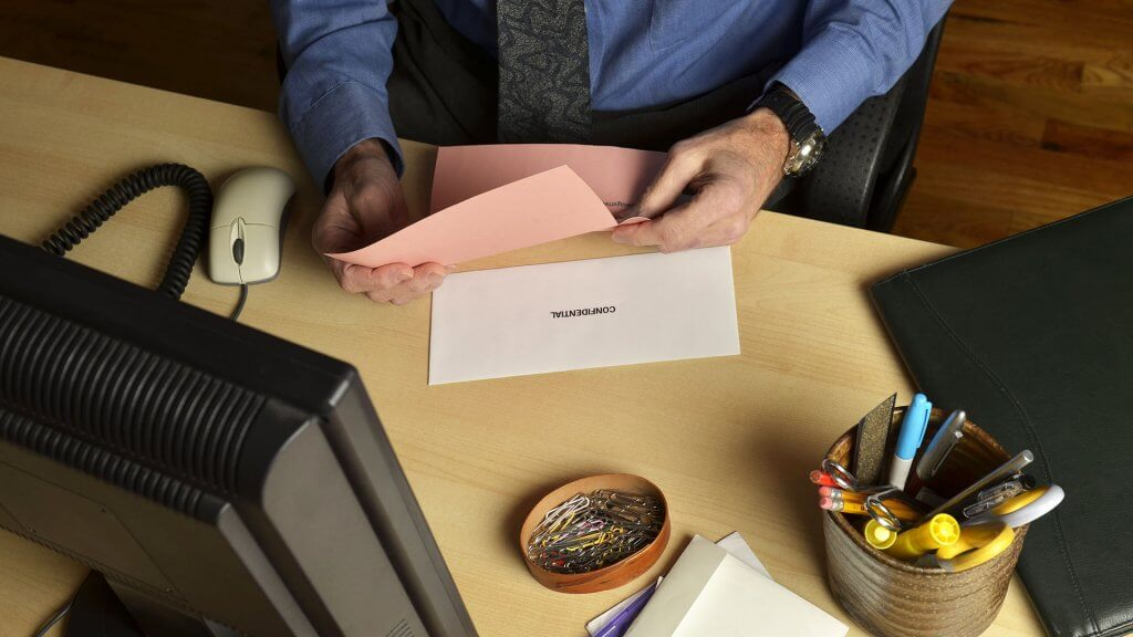 man opening confidential documents at his desk