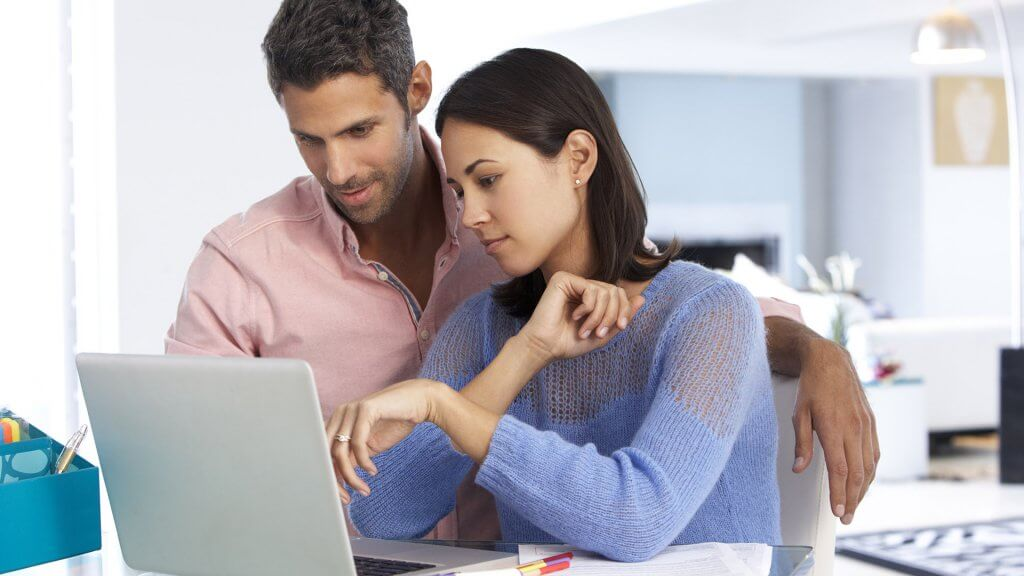 couple looking intently at something on their laptop