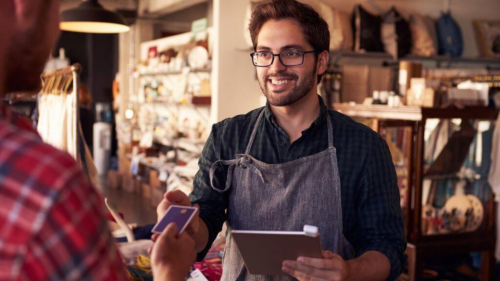male employee in apron receiving credit card from customer