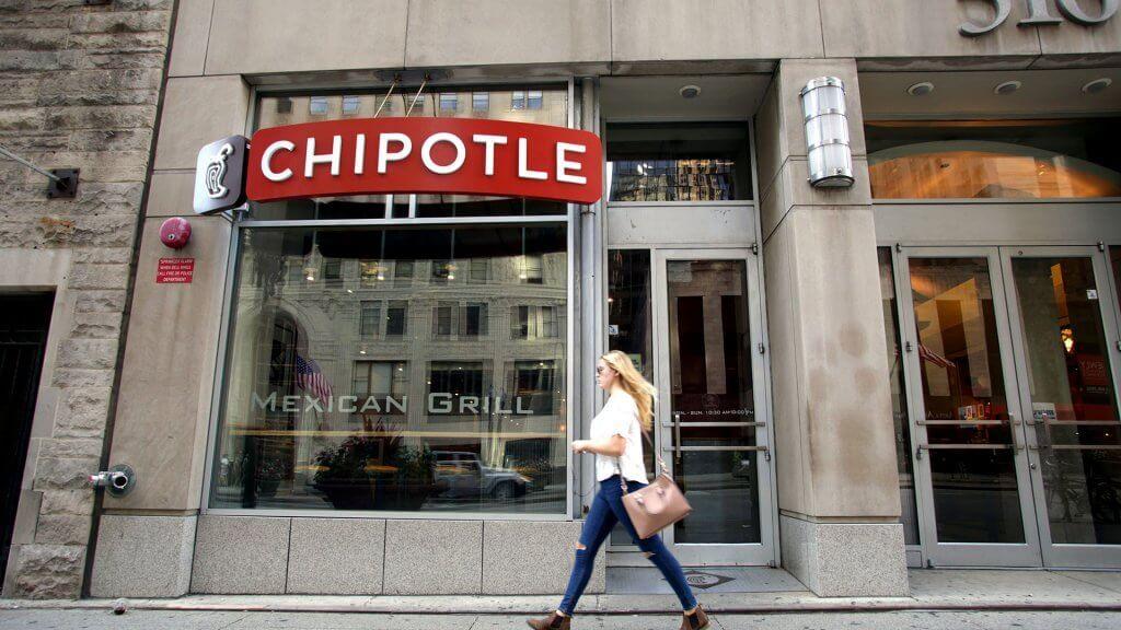 woman walking past a chipotle restaurant