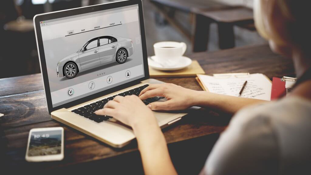 woman researching new cars on laptop