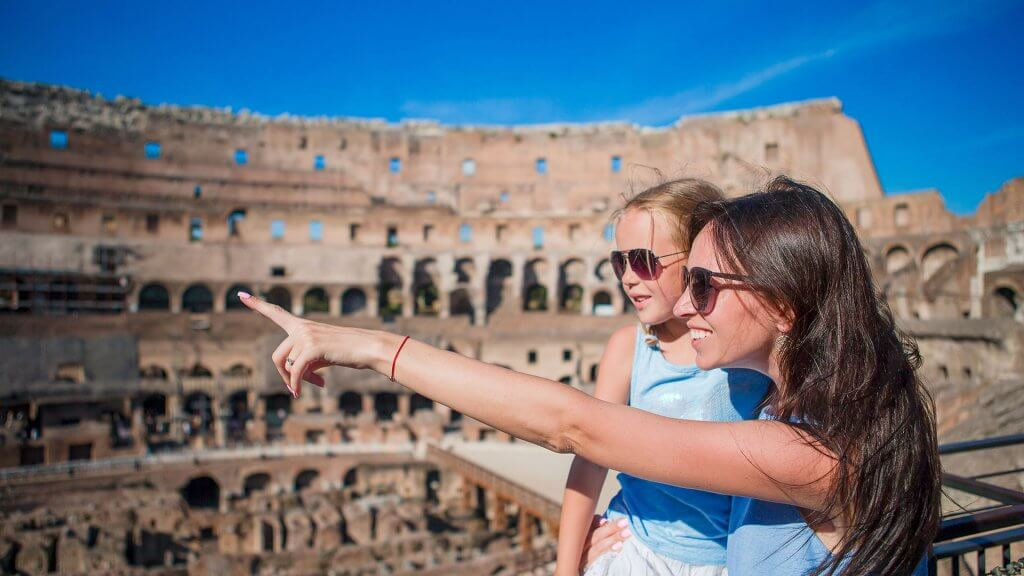 mom carrying daughter and pointing at something at the Colosseum in Rome
