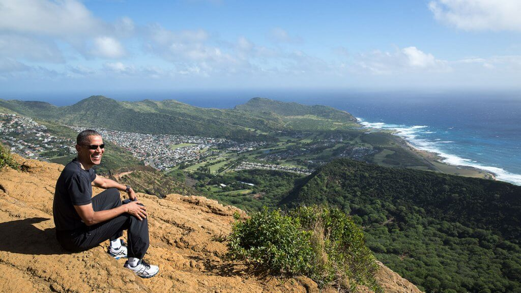 Barack Obama sitting on a hiking trail
