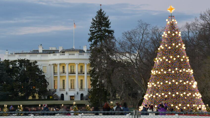 front street view of the white house with people taking pictures of the giant christmas tree near the perimeter