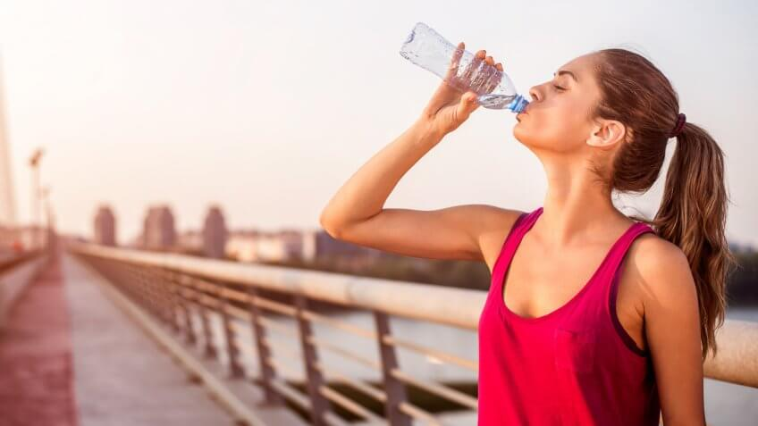 woman in workout attire drinking a plastic bottle of water