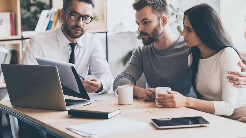 couple looking over finances with advisor