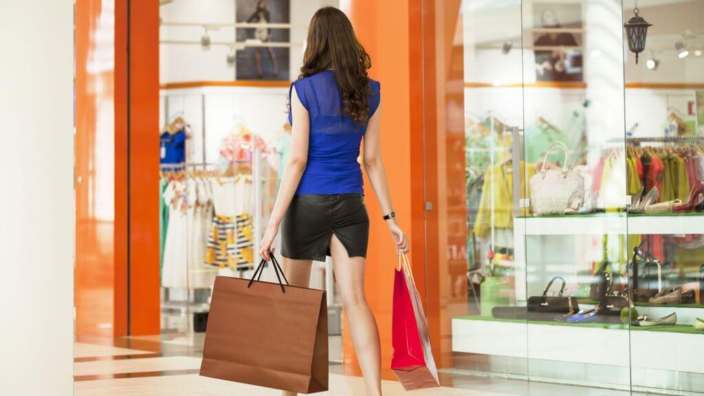 woman carrying two shopping bags inside a mall