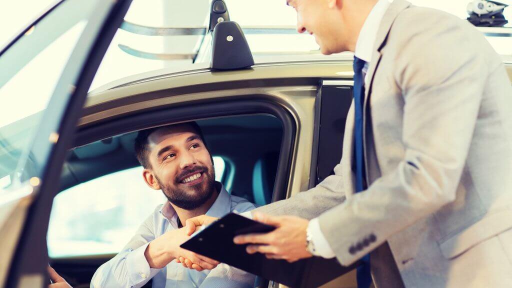 car salesman closing the deal with customer