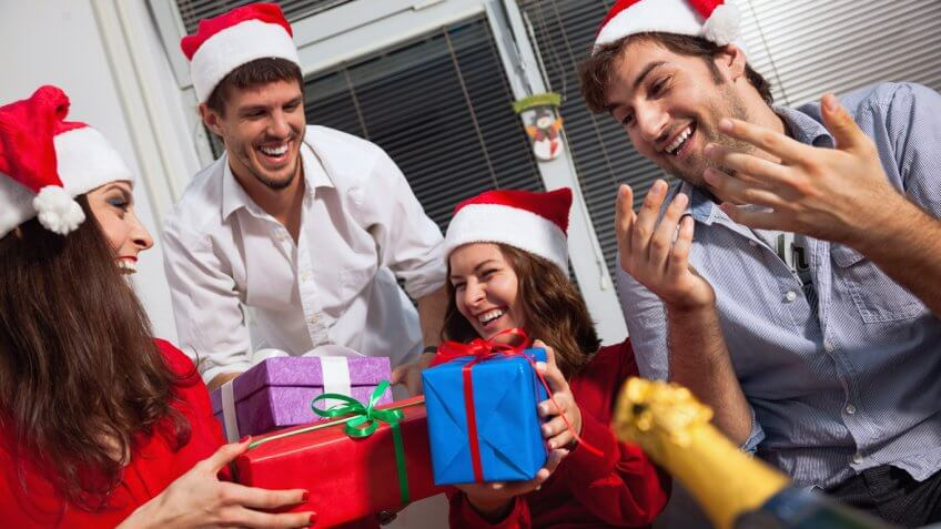 friends laughing and passing out christmas gifts