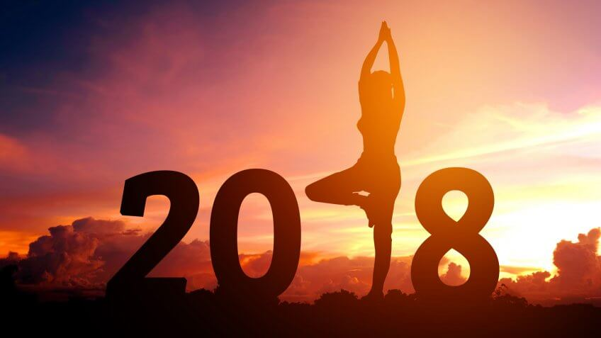 Silhouette young woman practicing yoga on 2018 new year.