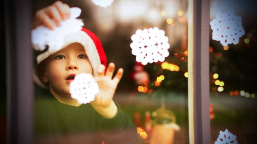 A young child is decorating a window with white paper snowflakes.