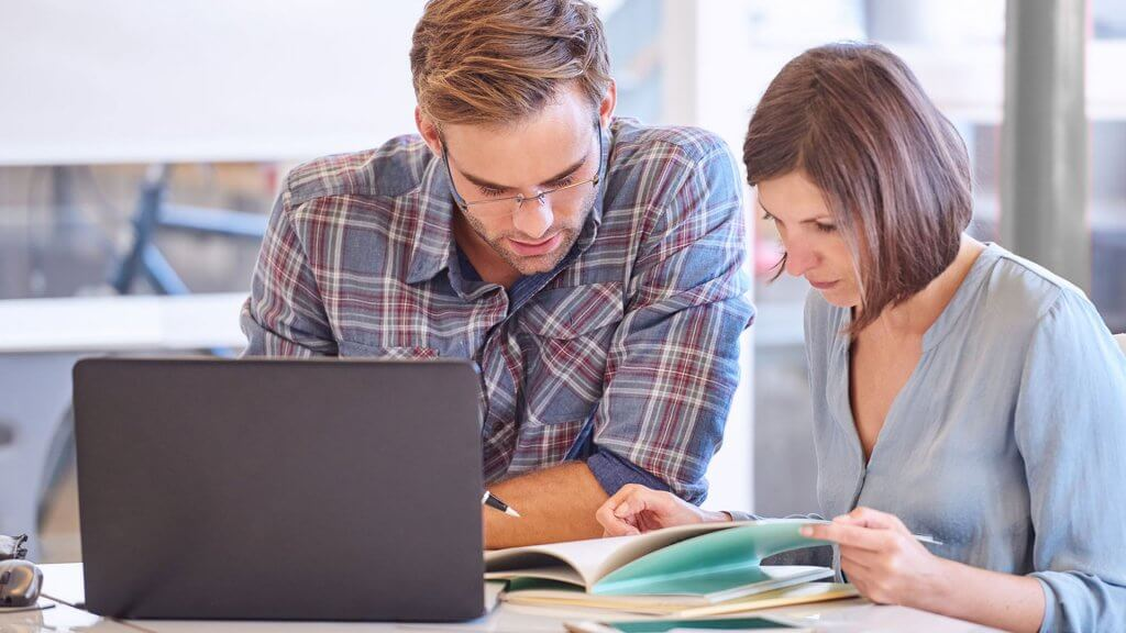 man and woman reviewing booklet