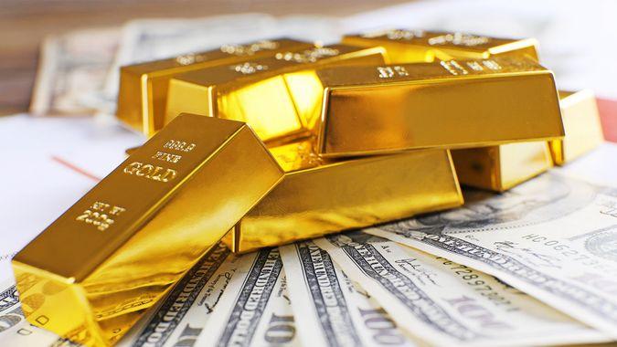 gold blocks on top of hundred dollar bills