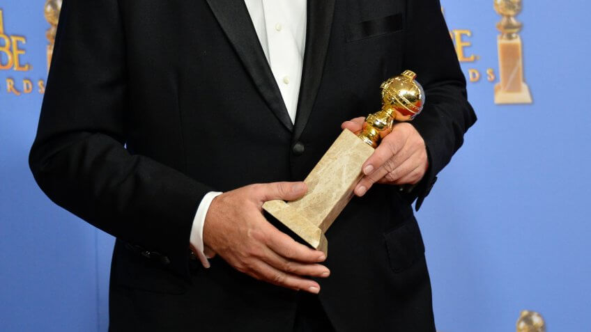 man holding golden globe