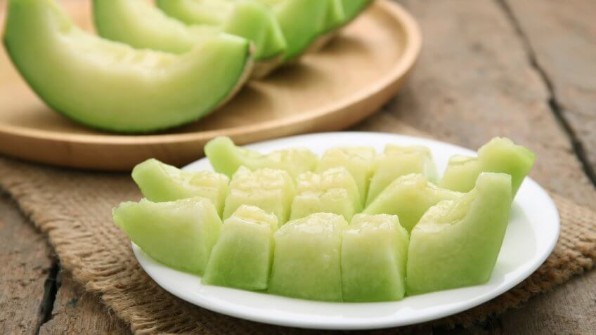 Green cantaloupe melon slices on wooden table.