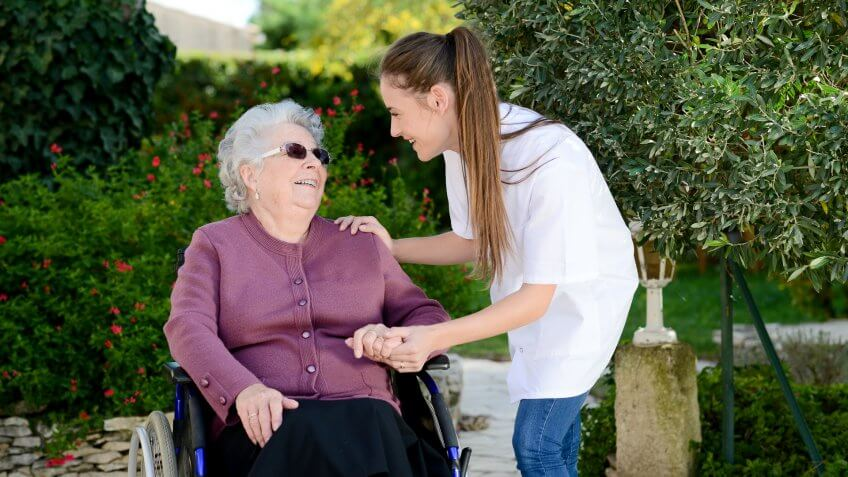 young woman attending elderly woman in a wheelchair