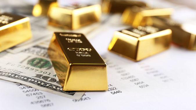 gold blocks on top of hundred dollar bills and data spreadsheet