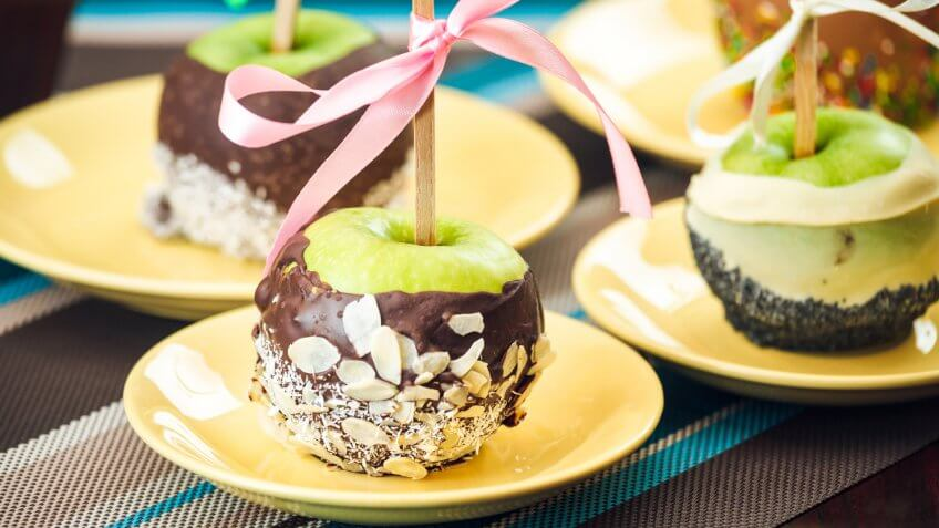 Group of Chocolate coated green apples on plates.