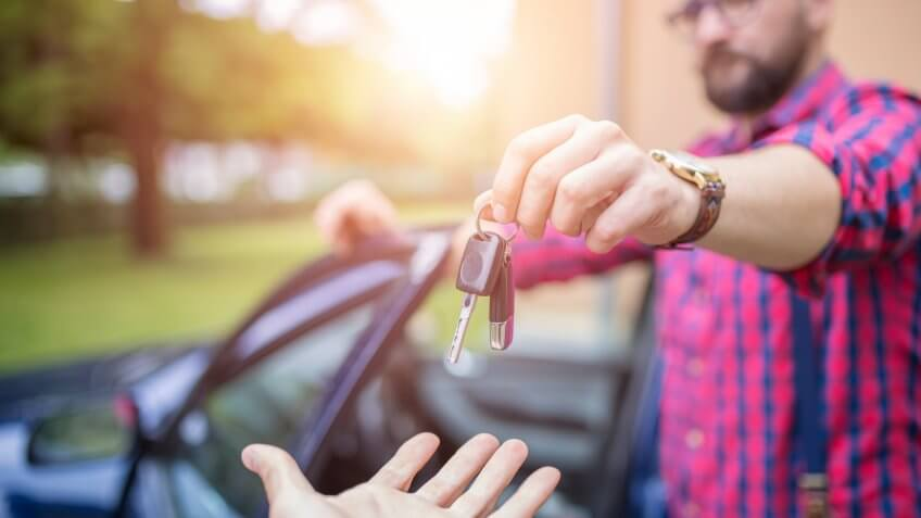 Man standing by the car and giving back car keys