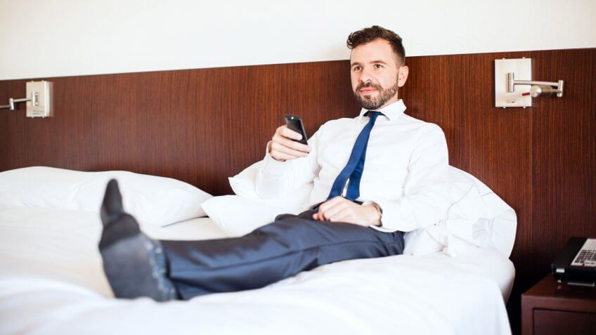man in suit laying on bed at hotel