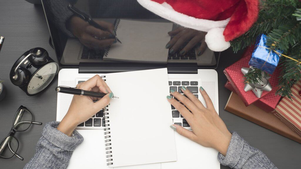 overhead shot of womans hands taking notes near christmas tree