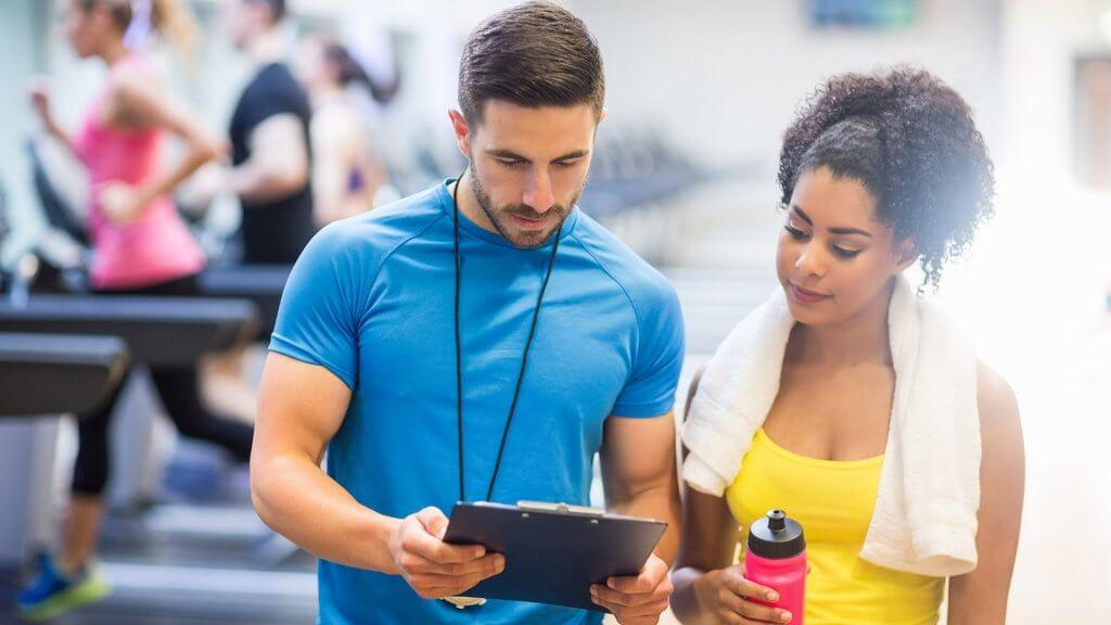 personal trainer looking at clipboard with woman