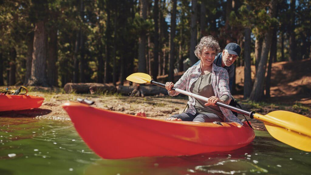 Woman rowing in kayak with help from man