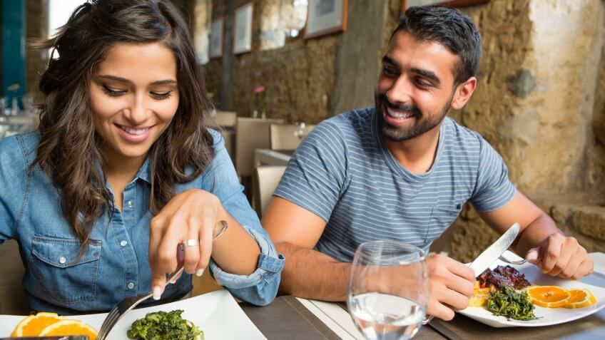 happy young couple eating at a restaurant
