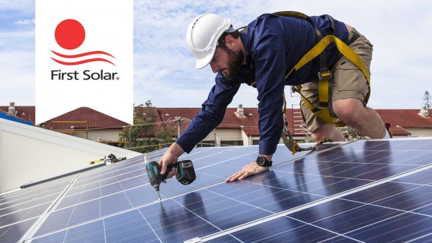 first solar logo with man installing solar panels as backdrop