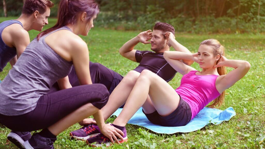 man and woman doing crunches outside while man and woman support them