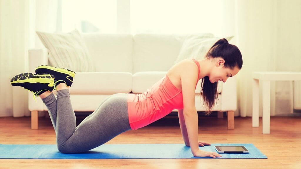 woman in pushup or yoga position and looking at tablet
