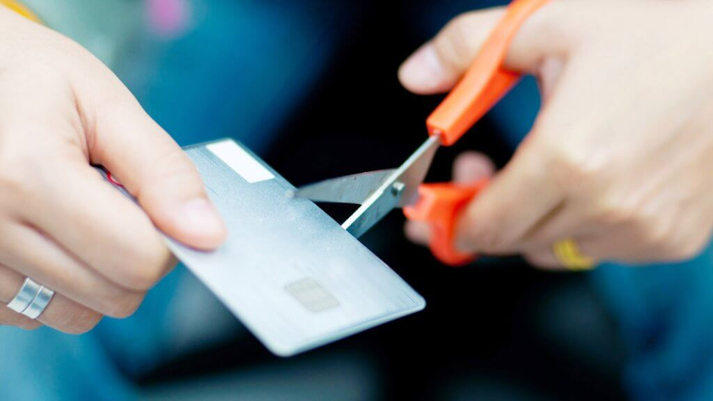 close up of hands cutting credit card