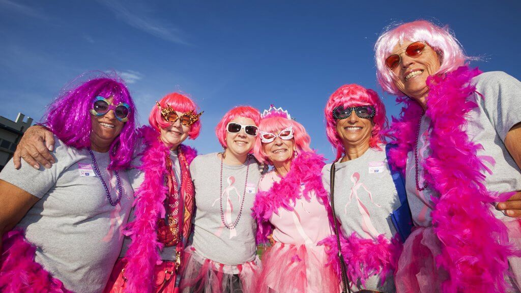 group of women dressed in garish pink wigs and accessories