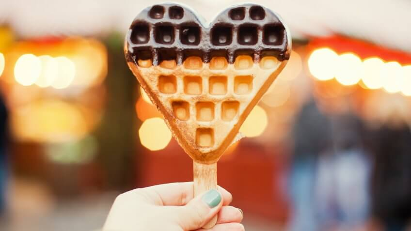 Heart-shaped freshly baked waffle in the hand.