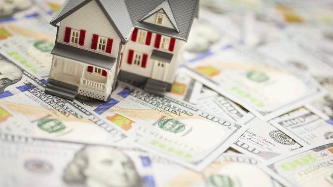 toy houses sitting on hundred dollar bills