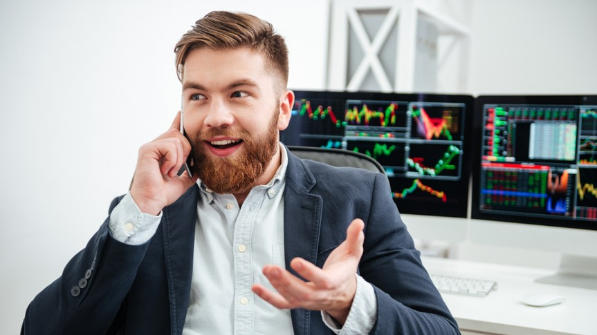 man enthusiastically on the phone with graphs and charts on the computer screen behind him