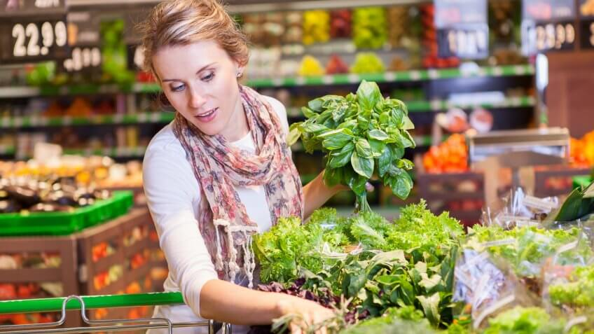 Woman picking up green vegetables in a grocery supermarket