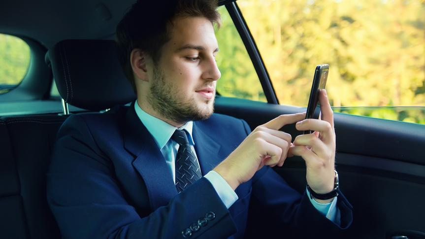 man in the back of a car on his cell phone