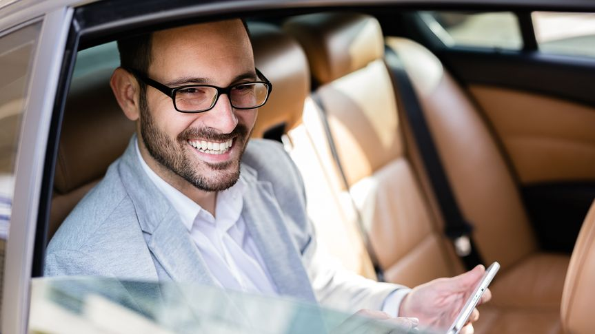 smiling man looking out of the window of a car