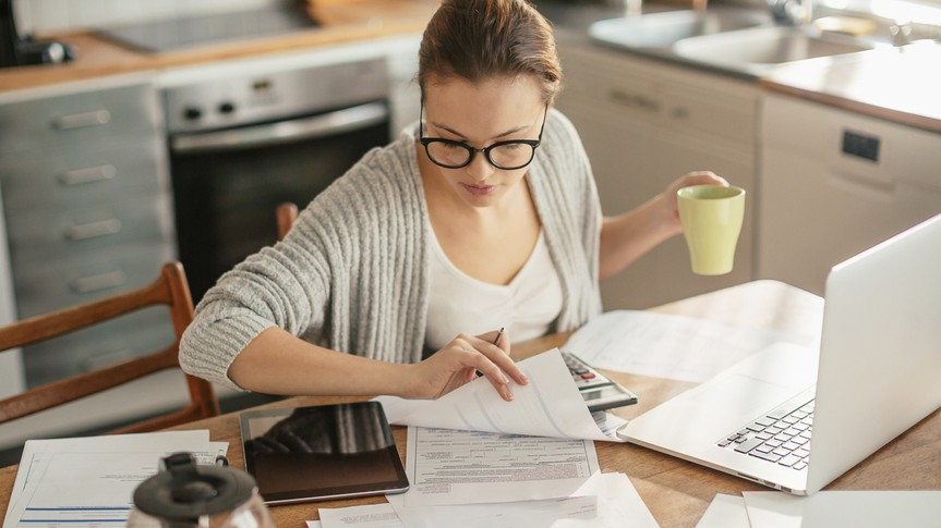 woman drinking coffee in her kitchen reviewing documents with a calculator, ipad and laptop next to her